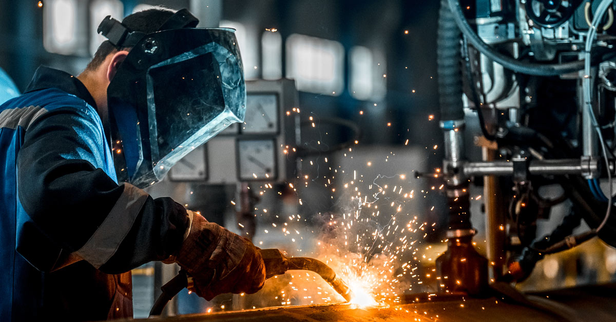 Man welding at oil and gas refinement centre